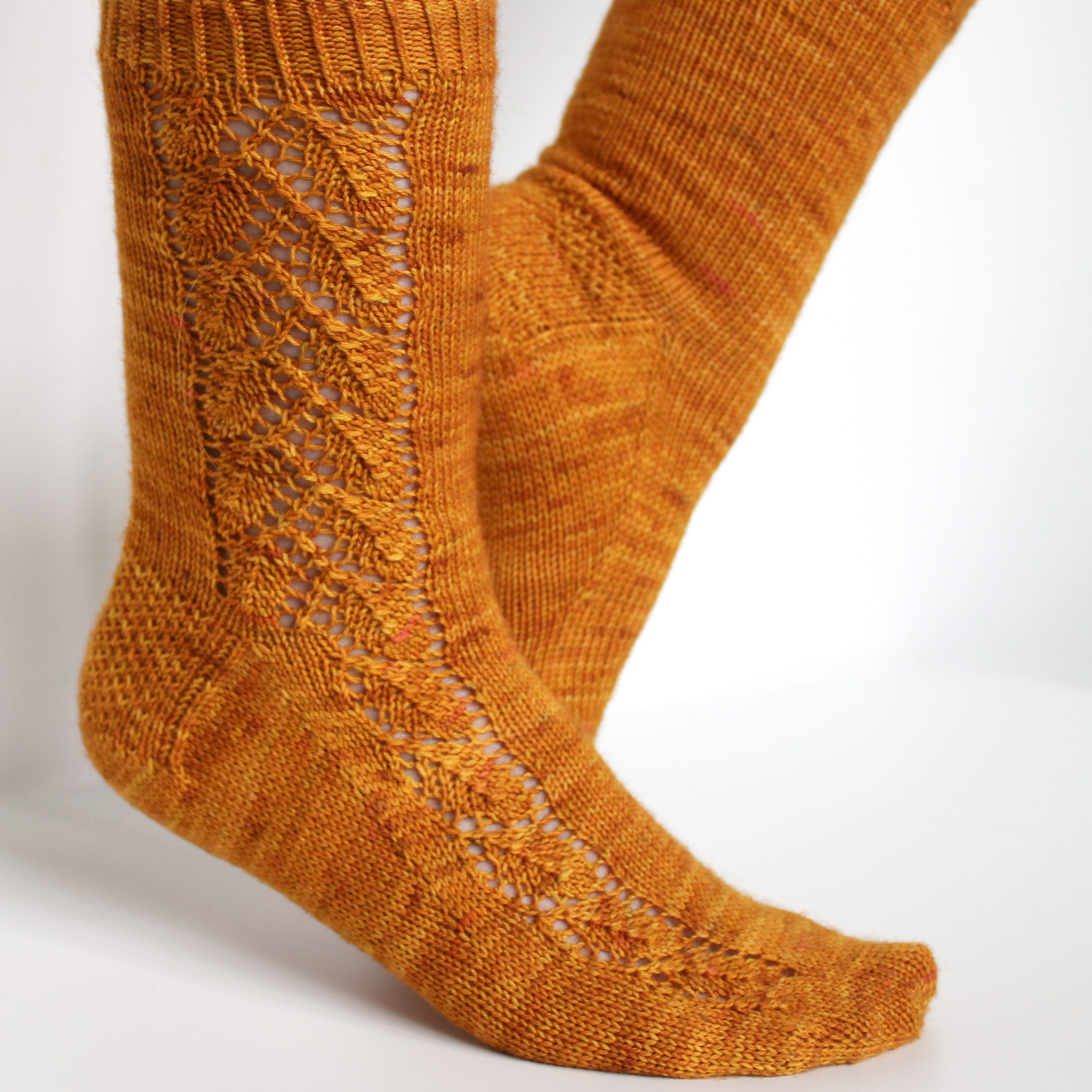Orange socks with a lace leaf pattern up the foot and leg