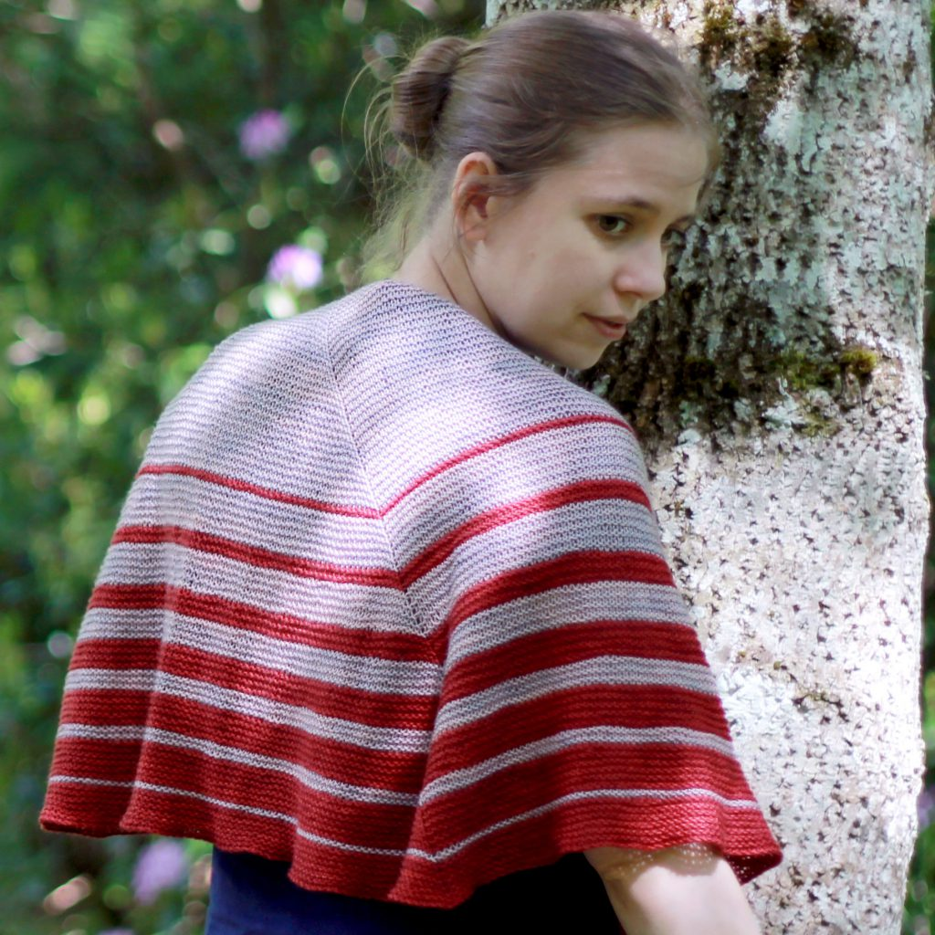 A crescent shaped shawl with graduated strips towards the edge
