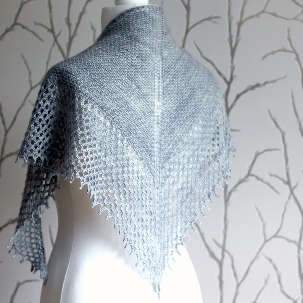 A grey shawlette with a textured body and wide lace border on a white mannequin.