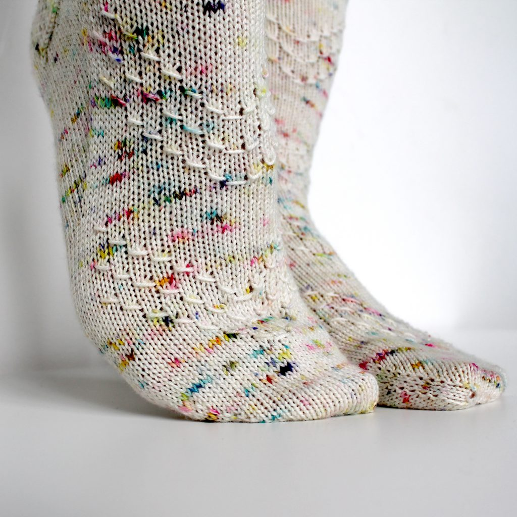 A speckled pair of socks with a textured chevron pattern