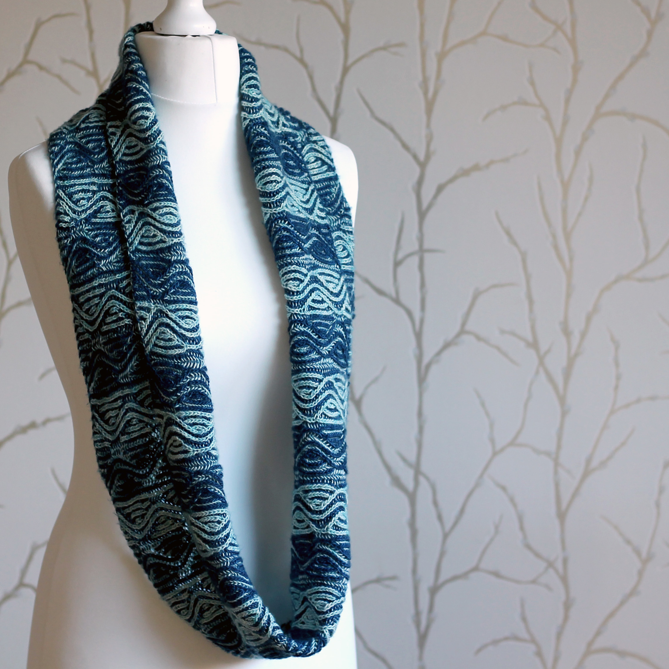 A mannequin displaying a long brioche cowl with dark and light blue vertical stripes and a faux cable pattern