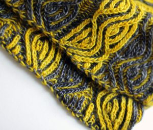 A close up on a brioche cowl with yellow and grey vertical stripes showing the cast-on and bind-off