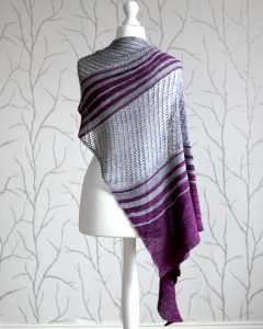 A purple and grey striped shawl with lace panels draped around a mannequin