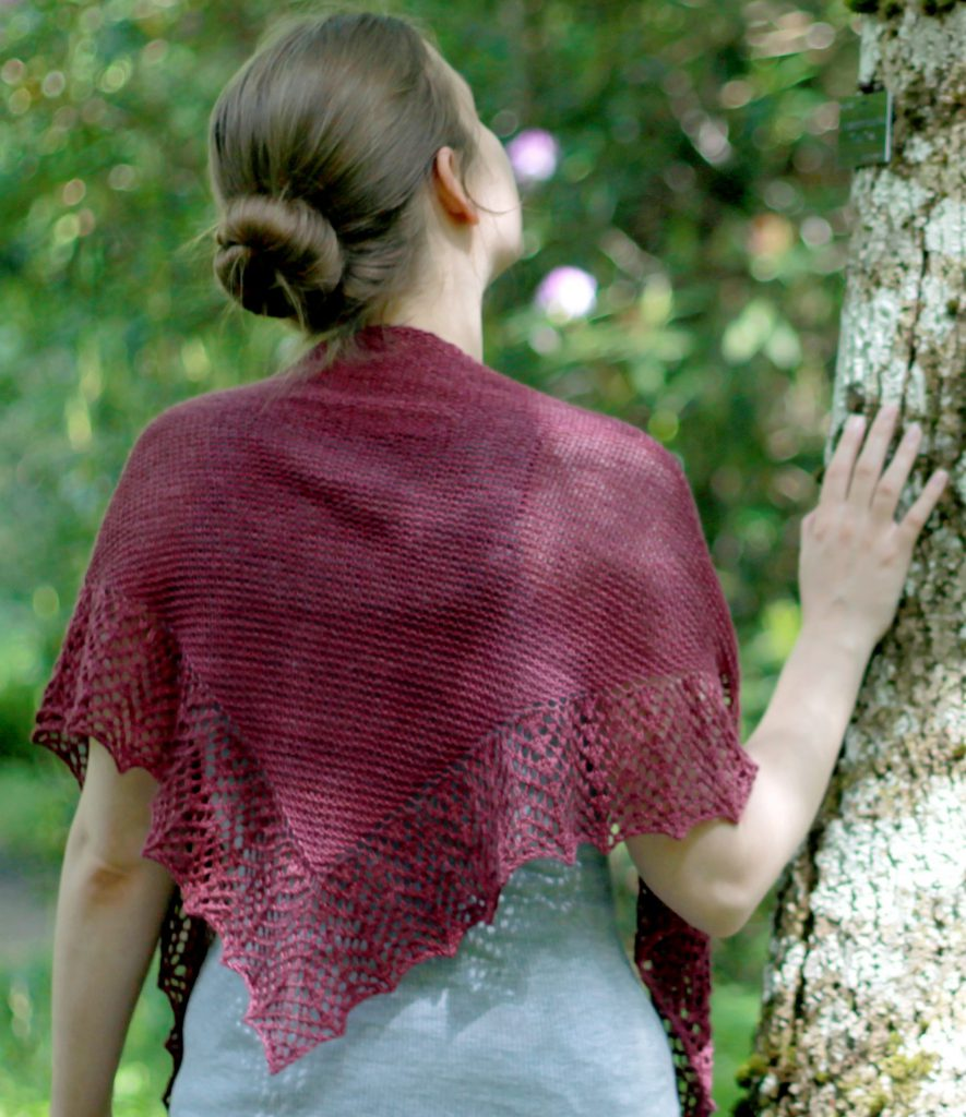 A triangular garter stitch shawl with a knitted on lace border