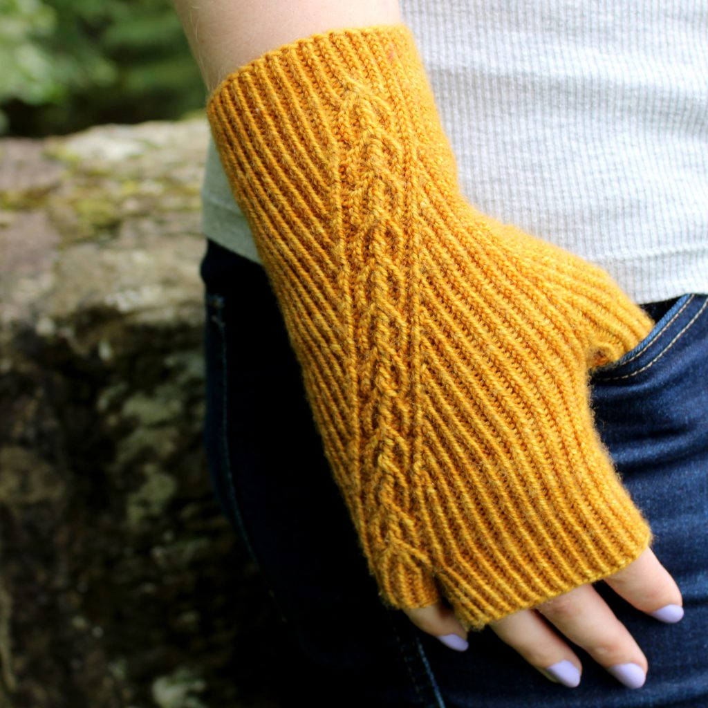 Twisted rib fingerless mitts with a narrow cable crossing the back of the hand from the inside of the wrist to the little finger. The little finger has a separate opening. Thumb is tucked into the jeans pocket of the model