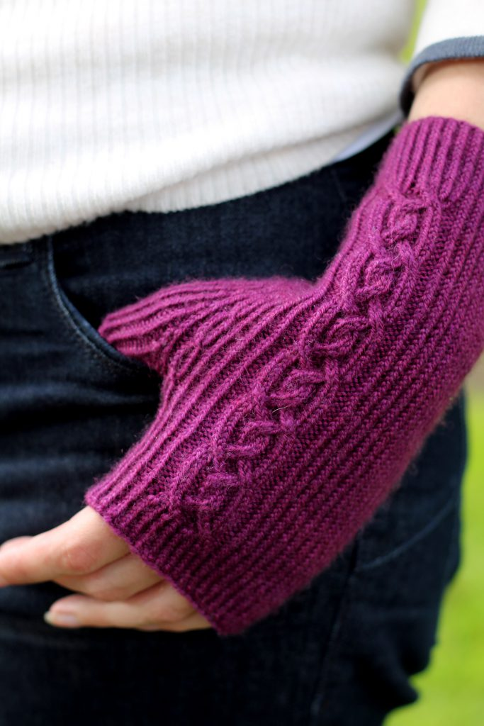 Twisted rib fingerless mitts with a large cable up the back of the hand and a narrow cable pattern that splits around the thumb (thumb tucked into jeans pocket)