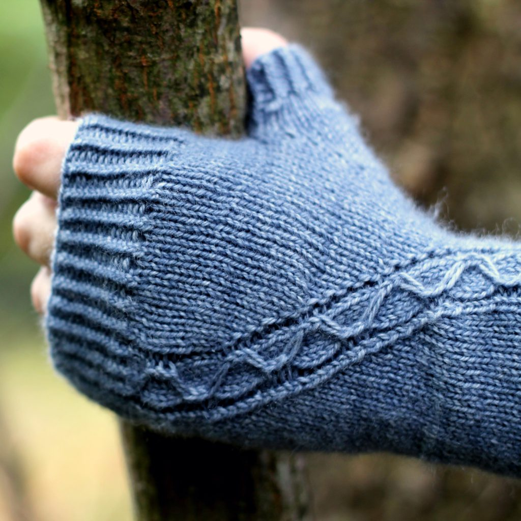 A blue fingerless mitt with a cable pattern travelling diagonally across the back of the hand, with the hand holding a tree branch